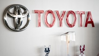 This picture shows a Toyota logo next to the Tokyo 2020 Olympic and Paralympic Games mascots and torch at a closed Toyota showroom in Tokyo on May 12, 2021.