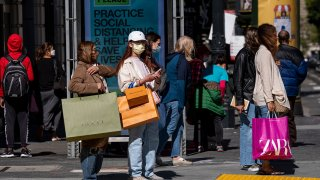 People wearing protective masks carry shopping bags while waiting to cross Geary Street in San Francisco