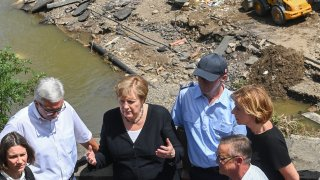 German Chancellor Angela Merkel (2ndL) and Rhineland-Palatinate State Premier Malu Dreyer (R) talk as they stand on a bridge during their visit in the flood-ravaged areas on July 18, 2021 in Schuld, near Bad Neuenahr-Ahrweiler, Rhineland-Palatinate state, western Germany. Extreme downpours caused devastating floods this week in Germany and other parts of western Europe devastating the region. The death toll across Germany and Belgium has risen to at least 180 as rescue workers continue their efforts and communities begin to clear the debris left by the receding waters.