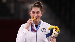 Gold medallist Anastasija Zolotic of the United States bites her medal at a victory ceremony for the women's -57kg taekwondo event during the Tokyo 2020 Summer Olympic Games, at the Makuhari Messe convention center.