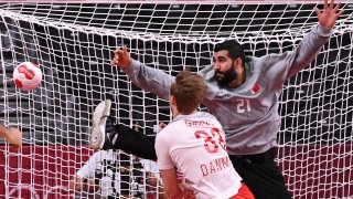 Bahrain's goalkeeper Mohamed A.Husain (R) fails to stop a shot during the men's preliminary round Group B handball match between Denmark and Bahrain of the Tokyo 2020 Olympic Games.