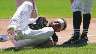 White Sox star Yoan Moncada lays on the ground, holding his right hand after suffering an injury on the basepaths during a game against the Twins