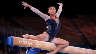 Suni Lee competes on the uneven bars