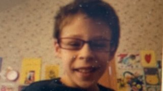 A missing Aurora child, wearing glasses and a black t-shirt, is featured in this image