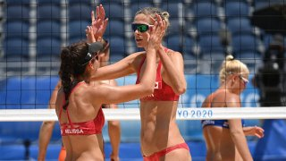 Canada's Melissa Humana-Paredes (L) celebrates winning with partner Sarah Pavan in their women's preliminary beach volleyball pool A match between Canada and the Netherlands during the Tokyo 2020 Olympic Games at Shiokaze Park in Tokyo on July 24, 2021.
