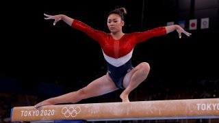 Sunisa Lee competes on the balance beam during the team final of the women's artistic gymnastics competition in Tokyo