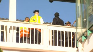Two uniformed CTA personnel, both wearing yellow reflective jackets, and two Chicago police officers stand behind a railing at a Green Line station