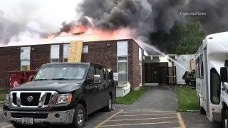 In the foreground, a black truck sits in front of a burning brick building, with flames shooting from the roof