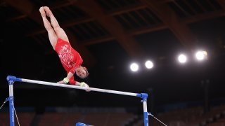 China's Xijing Tang competes on uneven bars during women's qualification