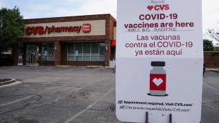 An information sign regarding COVID-19 vaccines is seen outside of a CVS store in Chicago, Ill.