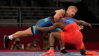 Kyle Dake, top, competes against Cuba's Jeandry Garzon Caballero during their men's freestyle 74kg repechage wrestling match at the 2020 Summer Olympics, Friday, Aug. 6, 2021, in Chiba, Japan.