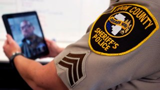 Sheriff's Police Sgt. Bonnie Busching tests a virtual meeting with a tablet at the Cook County Sheriff's Office in Chicago.