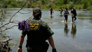 FILE - In this June 15, 2021, file photo a Border Patrol agent watches as a group of migrants walk across the Rio Grande on their way to turn themselves in upon crossing the U.S.-Mexico border in Del Rio, Texas. The Biden administration proposed Wednesday, Aug. 18, to change the way asylum claims are handled, aiming to cut a huge backlog of cases from the Southwest border that has resulted in people waiting years to find out if they will be allowed to stay in the U.S.