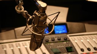 Radio station microphone in front of mixing board.