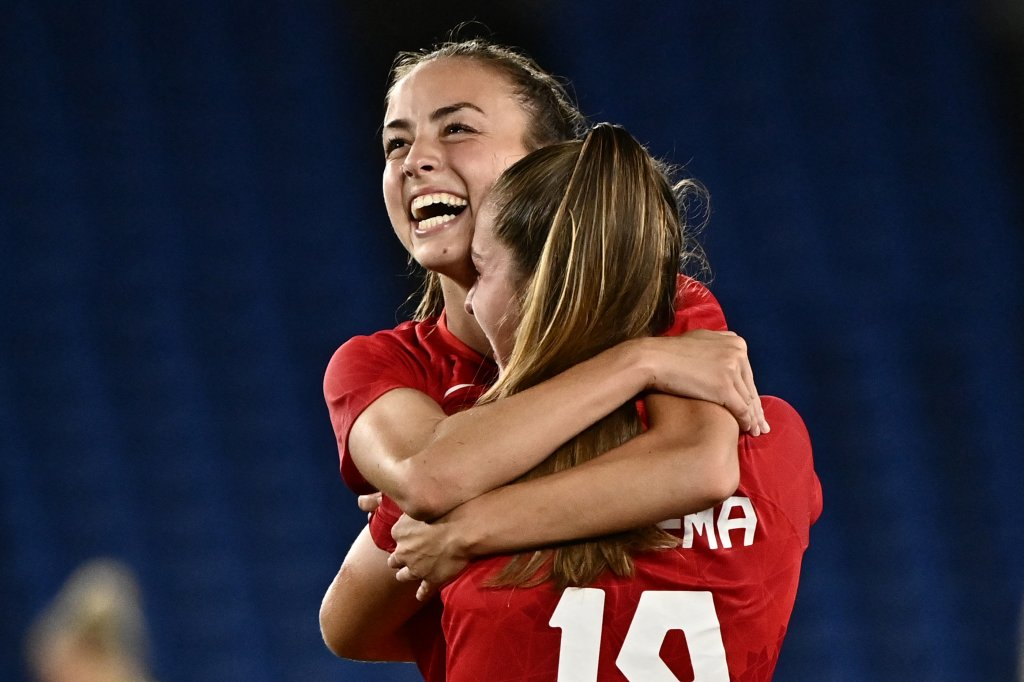 Canada's midfielder Julia Grosso, left, hugs forward Jordyn Huitema after scoring the winning penalty during the penalty shoot-out of the Tokyo 2020 Olympic Games women's final football match between Sweden and Canada at the International Stadium Yokohama in Yokohama on Aug. 6, 2021.