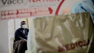 A South African man seats as he waits for his first dose of Pfizer Covid-19 vaccine, in Zwartkops Raceway drive-through vaccination site in Centurion on August 13, 2021.