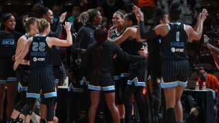 The Chicago Sky, dressed in black uniforms with blue trim and lettering, celebrate a win over the Connecticut Sun in the WNBA semifinals