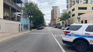 A photo shows West Division Street in Chicago during a SWAT situation, with a white and blue police SUV and red crime scene tape