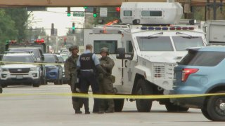 Three members of a Chicago SWAT team stand next to a white armored vehicle on West Division Street in Chicago