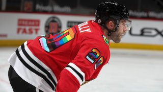 Blackhawks forward Brett Connolly, wearing a red jersey with a rainbow color pattern on the numbers, waits for his turn to shoot during warmups before a game