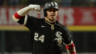 Yasmani Grandal, wearing a black White Sox jersey and black helmet with white lettering, pumps his fist and rounds the bases after hitting a home run against the Astros in the American League Division Series