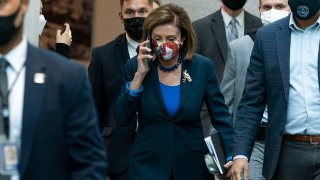House Speaker Nancy Pelosi of Calif., talks on her phone as she arrives for a meeting with House Democrats, Oct. 1, 2021, on Capitol Hill in Washington.