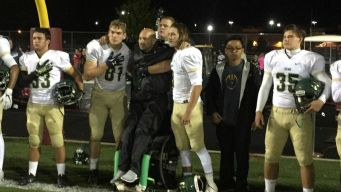 Football Players Help Coach Stand During National Anthem