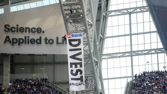 Photos: Pipeline Protestors Hang From Rafters at Bears Game